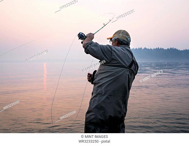 Senior Caucasian male fly fishing for salmon and sea run cutthroat trout off the coast