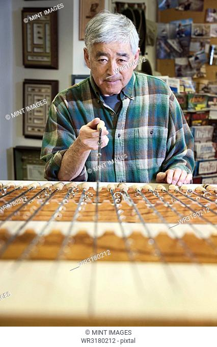 Asian American senior male checking the balance on a 5 weight fly fishing rod for sale in a fly fishing shop