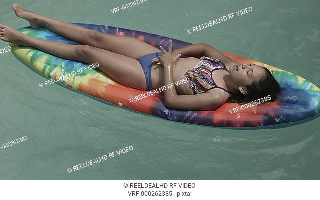 Girl lying on air bed and boy playing with her in swimming pool
