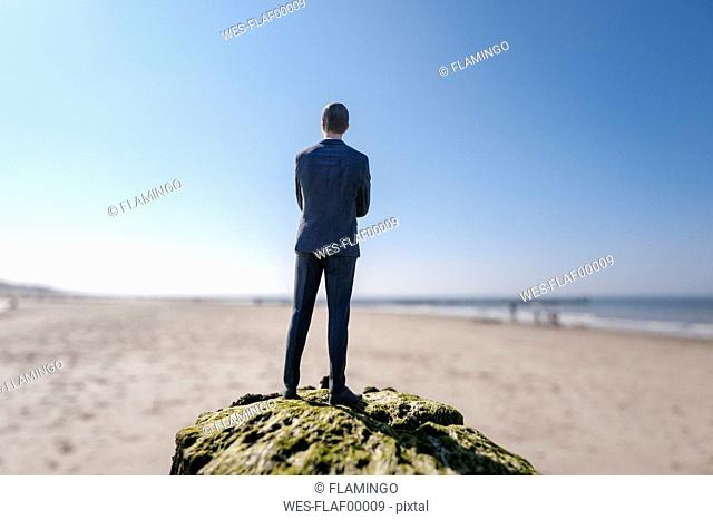 Businessman figurine standing on sand hill looking at view