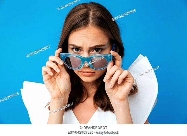 Portrait of a confused young girl in summer clothes looking over sunglasses isolated over blue background
