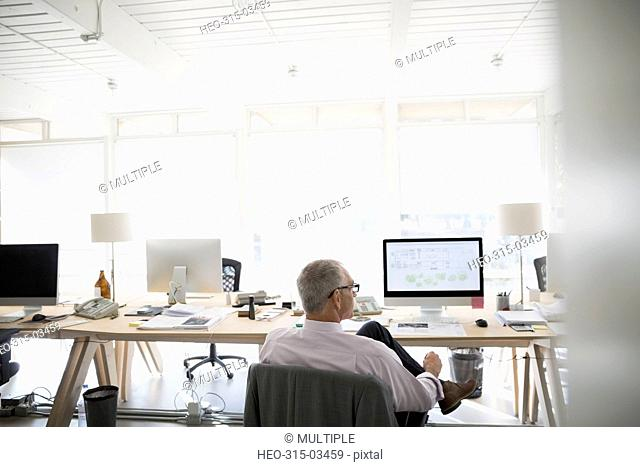 Male architect working at computer with digital blueprint in office