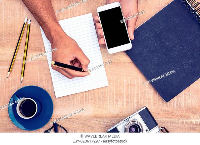 High angle view of businessman writing on notepad