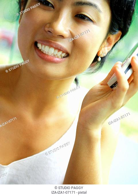 Close-up of a young woman holding a mobile phone and smiling