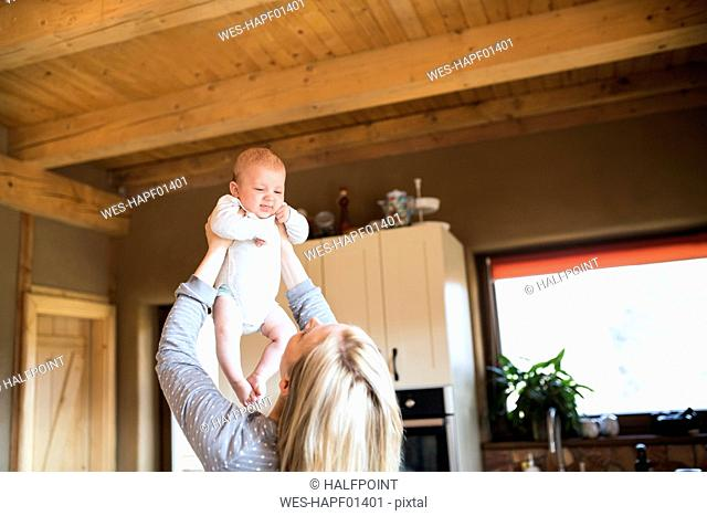 Mother lifting up baby at home