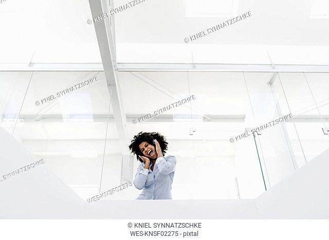 Young woman with headphones screaming in office