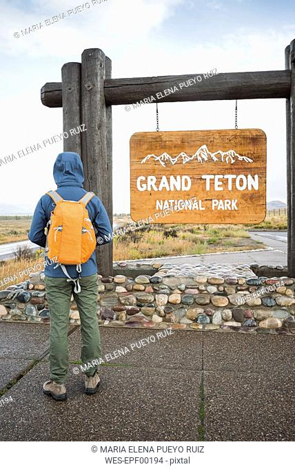 USA, Wyoming, back view of man with backpack standing at entrance of Grand Teton National Park
