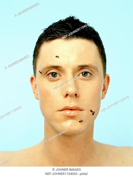 Portrait of young man with ants on face