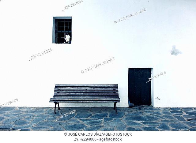 Cat in window, bench & door. Cadaques, Catalonia, Costa Brava, Girona, Spain