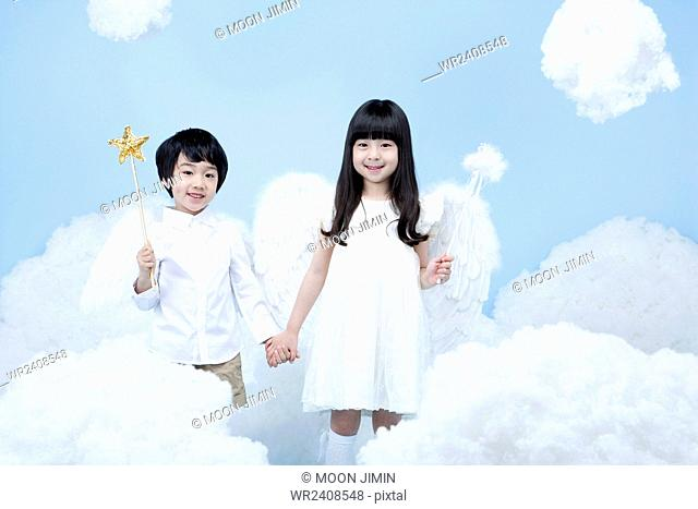 Boy and a girl holding a magic stick each in the background representing heaven