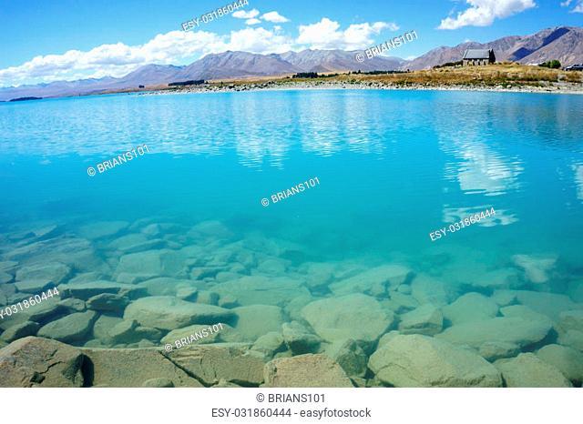 Natural turquoise Lake Tekapo and rocky edge, New Zealand