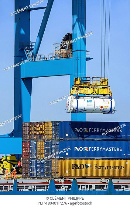 Dockworkers operating gantry crane / portainer crane/ portal crane in the port of Zeebrugge / Zeebruges along the North Sea coast, Flanders, Belgium