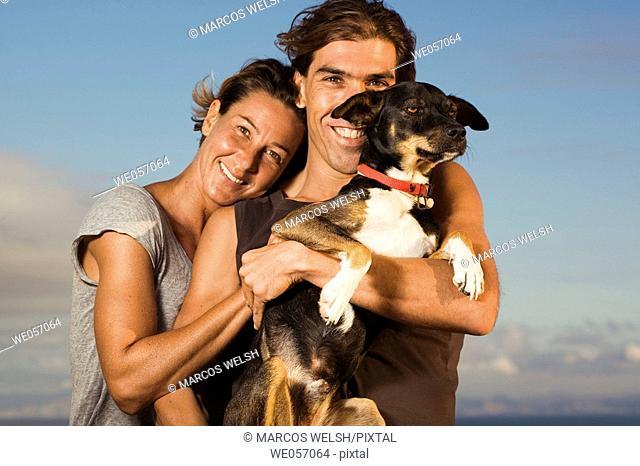 Couple Hugging Their Dog