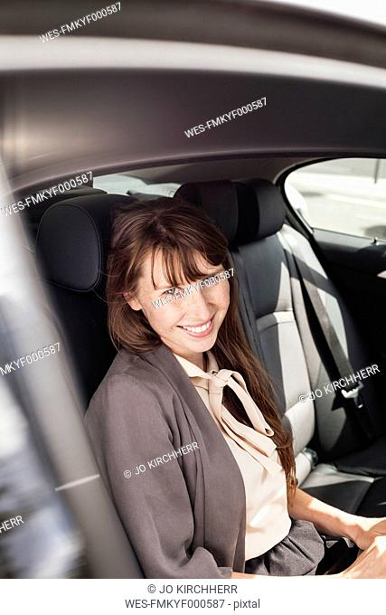 Germany, portrait of smiling businesswoman sitting in a car
