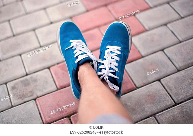 Legs in blue shoes at tile