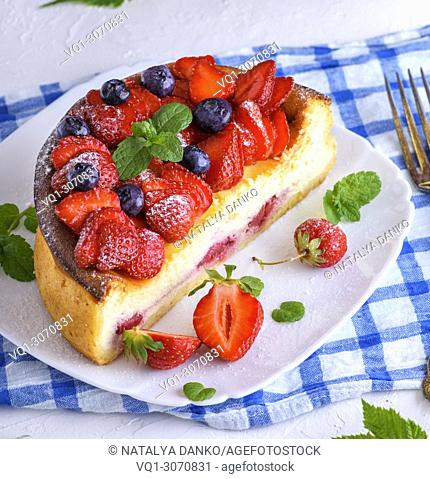 Cheesecake of cottage cheese and fresh strawberries on a white ceramic plate