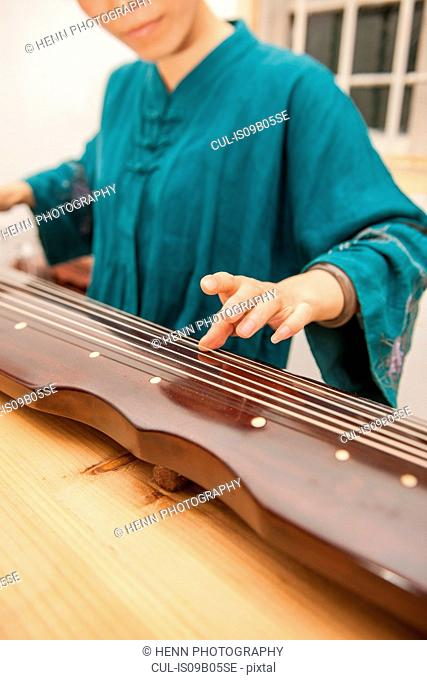 Chinese woman is playing the traditional Guzheng string instrument, Hezhou, Guangxi, China