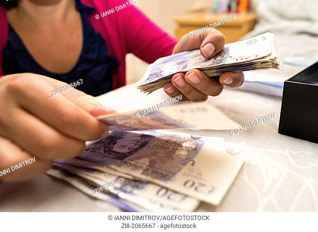 Woman counting money,UK pound sterling-close-up