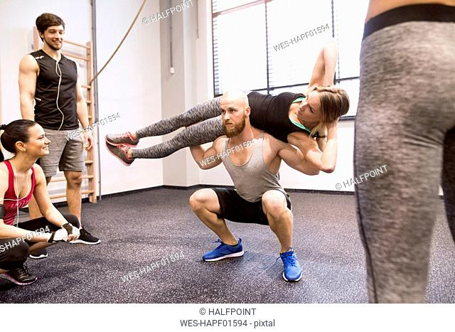 Young people doing fitness training in gym, lifting partners