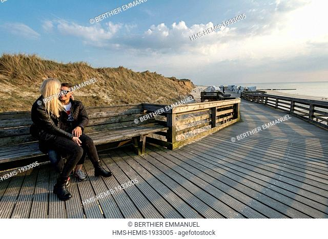 Germany, Schleswig-Holstein, Sylt in the Frisian Islands, couple at sunset on pontoon on Kampen beach