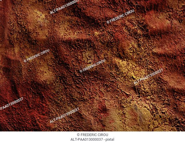 Warm-toned pigments on textured surface, close-up, full frame