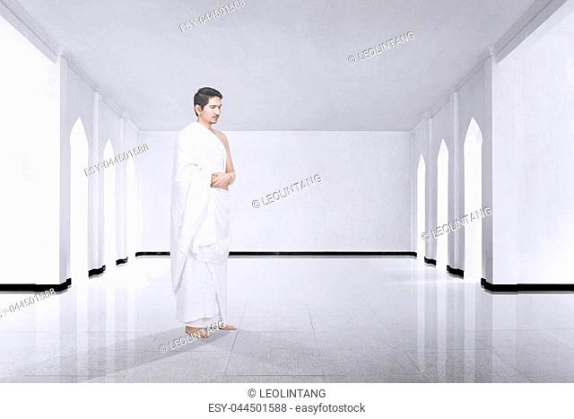 Photo of asian muslim man with ihram cloth praying inside the mosque