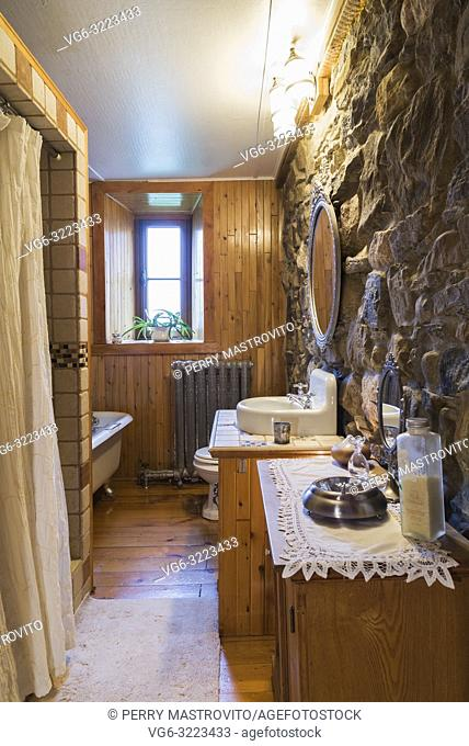 Main bathroom with claw-foot bathtub and ceramic shower stall on the ground floor inside an old circa 1752 Canadiana style fieldstone house