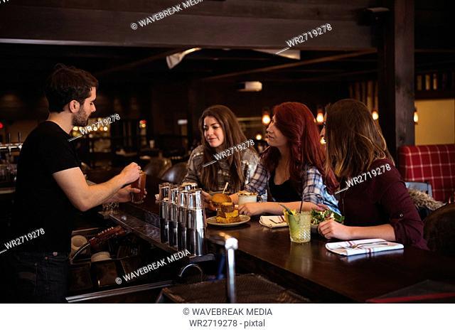 Friend enjoying drink at bar counter