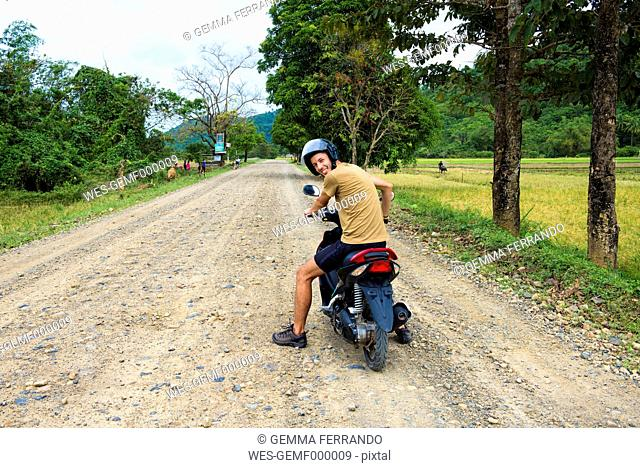 Philippines, Palawan island, man driving a motorcycle on a dirt road near El Nido