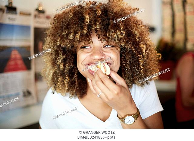 Black woman biting sandwich