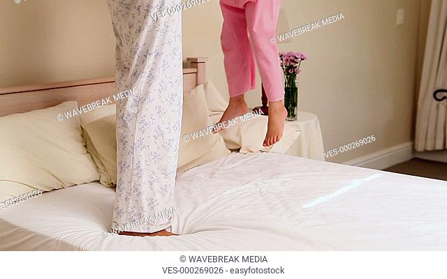Little girl bouncing on bed with her mother