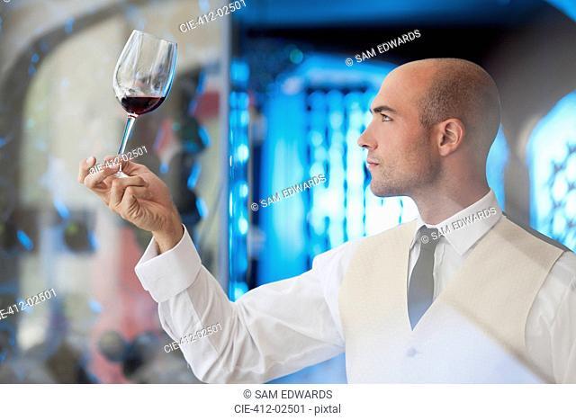 Waiter examining glass of wine in restaurant