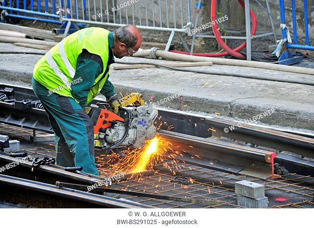 worker with abrasive cut-off machine working on tram lines, Czech Republic, Prague
