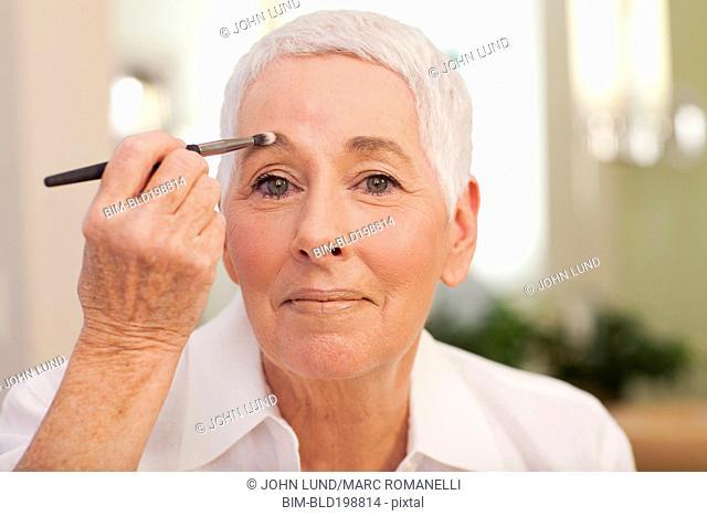 Senior Caucasian woman putting on makeup
