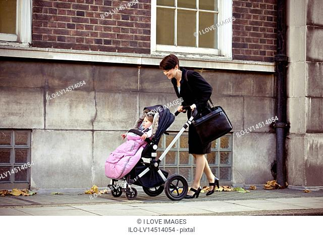 A mother pushing a stroller in the street