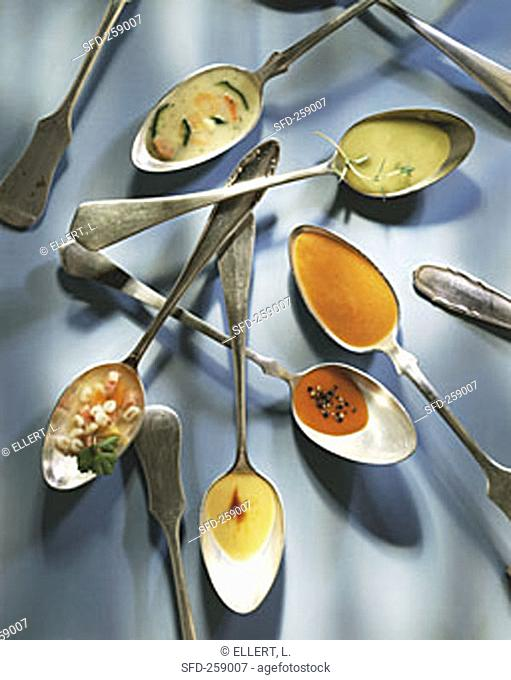 Different soups on spoons
