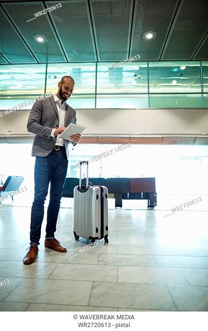 Businessman using digital tablet in waiting area