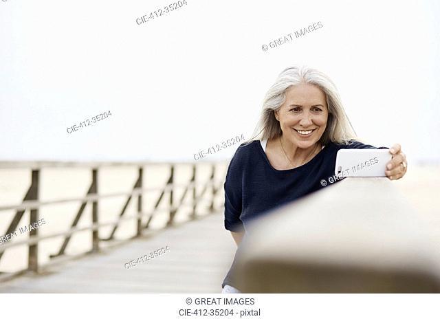 Smiling senior woman taking selfie with camera phone on beach boardwalk