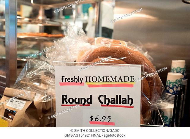 Round challah bread for the Jewish high holiday of Rosh Hashanah (New Year) at a special counter with a sign reading 'Freshly homemade round challah' at Izzy's...