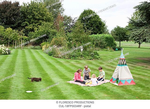 Children having picnic beside teepee