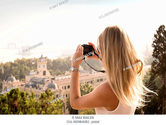 Woman with camera sightseeing, Malaga, Spain