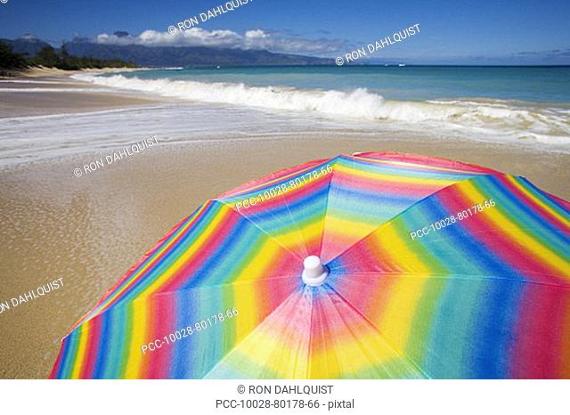 Brightly colored beach umbrella on the sand near the ocean