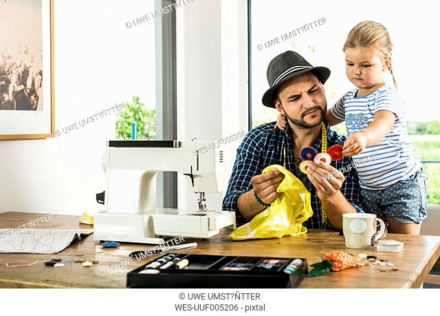 Father with and daughter sewing at home
