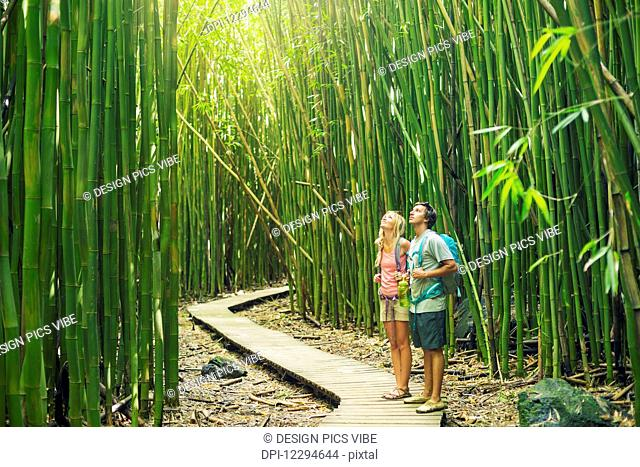 Couple having fun together outdoors on hike through amazing bamboo forest trail