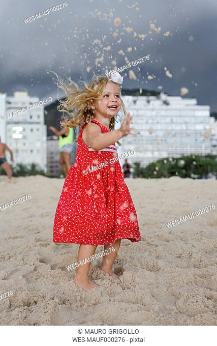 Brasil, Rio de Janeiro, girl playing with sand on Copacabana beach