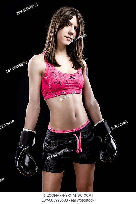 Boxing woman, pretty young boxing standing and defending by hands black box gloves isolated on a black background