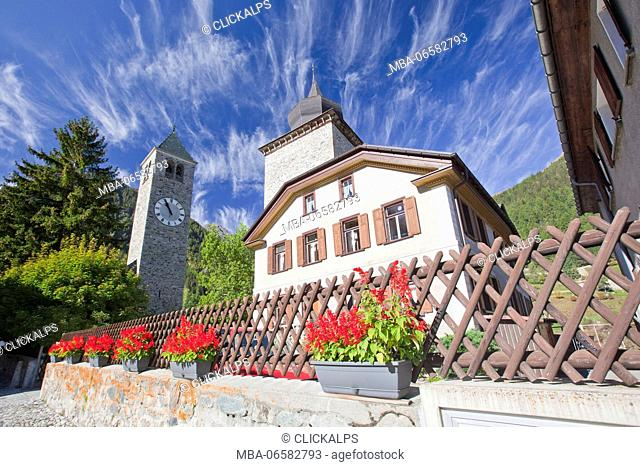Flowers blooming by the church in Susch and unusual clouds up in the sky, Engadine, Switzerland Europe