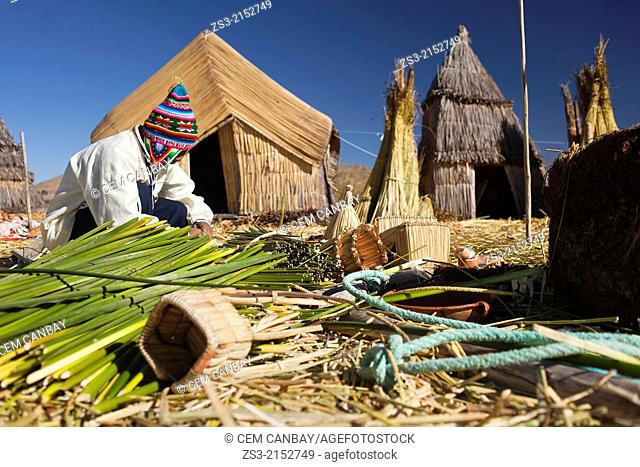 Aymara indigenous man working with Totora reeds, Uros Islands, Lake Titicaca, Puno Region, Peru, South America