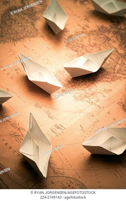 Group of small folded origami paper boats in ocean areas on top of old folded map