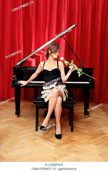 Beautiful, sensuous, woman, sitting on a stool in front of a grand piano, absorbing the scent of a rose